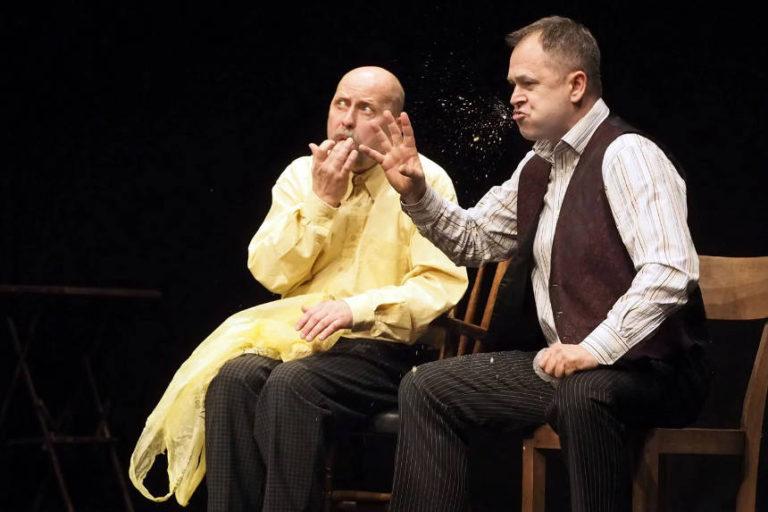 Zdjęcie przedstawia dwóch mężczyzn wśrednim wieku. Siedzą nakrzesłach stojących obok siebie, przodem dowidowni. Tło jest czarne. Mężczyzna zlewej jest łysy. Prawą ręką wkłada sobie coś doust, drugą przytrzymuje nakolanach plastikową siatkę nazakupy. Zatroskany spogląda wprzestrzeń przedsobą. Ciemnowłosy mężczyzna poprawej stronie mówi coś zpasją, wyrzucając zust fontannę okruchów. Prawą dłonią zszeroko rozstawionymi palcami sięga przedsiebie.